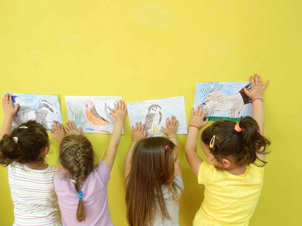 Quattro bimbe di spalle appoggiano i loro disegni sul muro. Un tasso, un pappagallo, una civetta e un istrice.