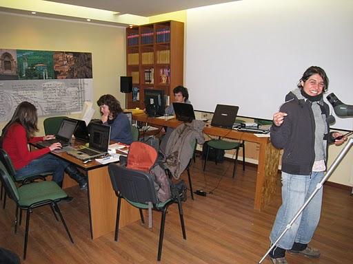 Tre ragazze che studiano al computer e una in primo piano che sorride alla telecamera