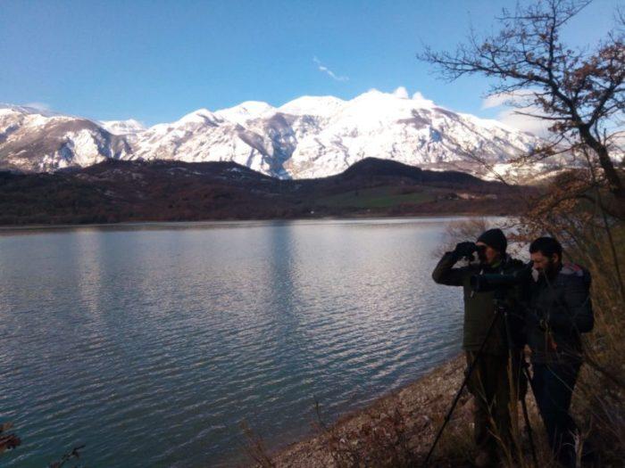 Due membri dello IAAP monitorano il territorio delle aree protette, una montagna innevata gli fa da sfondo